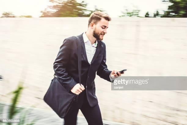Businessman Walking, Checking Phone