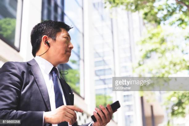 Affärsman gick nedför en väg medan du använder denna smarta telefonen