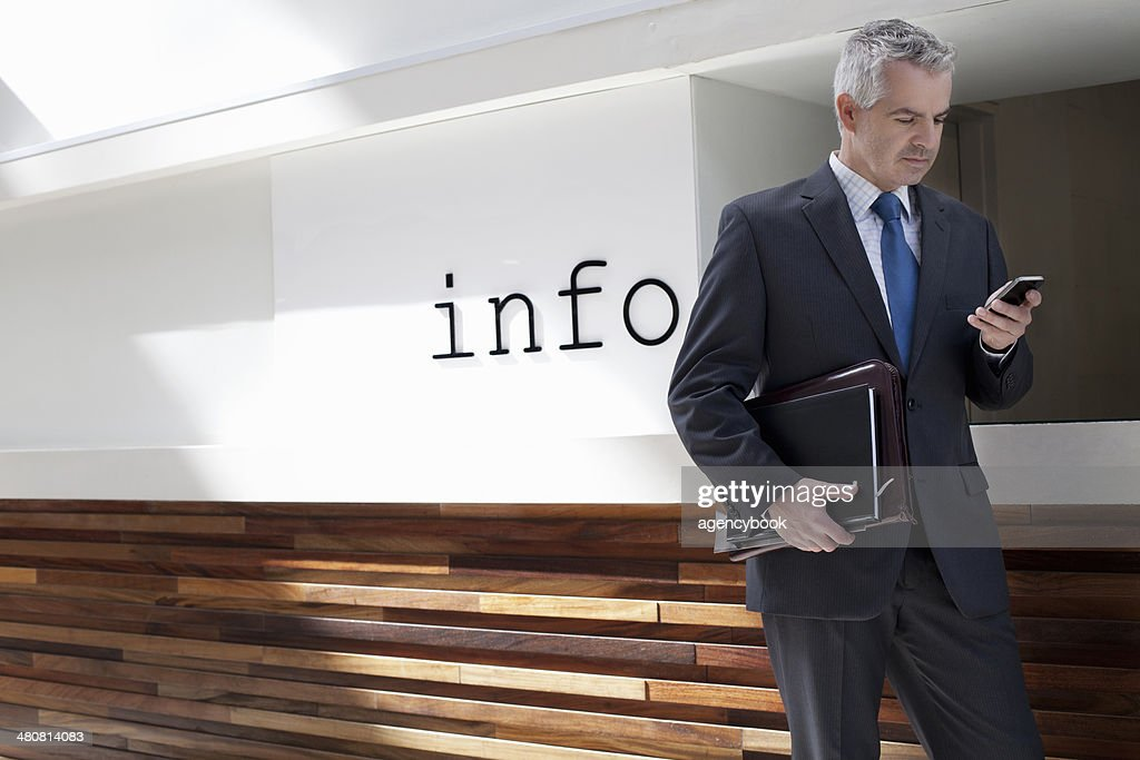 Businessman walking down corridor in office : Stock Photo