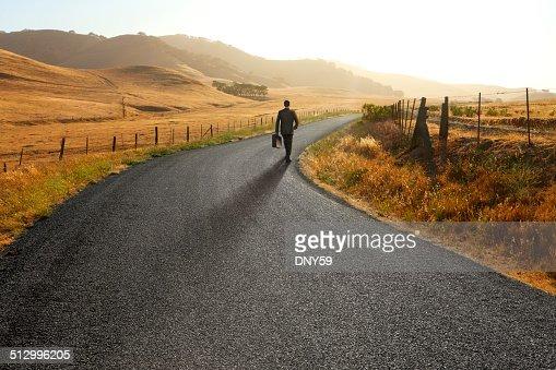Businessman walking down curving rural road