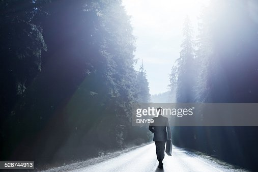 Businessman Walking Down Middle Of Road