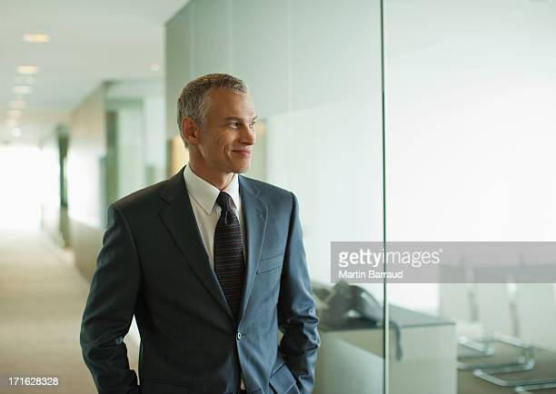 Businessman walking down modern office corridor
