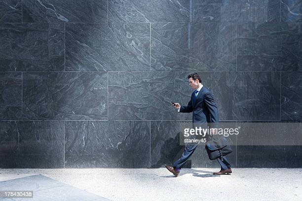 Businessman walking down the street with his cell phone