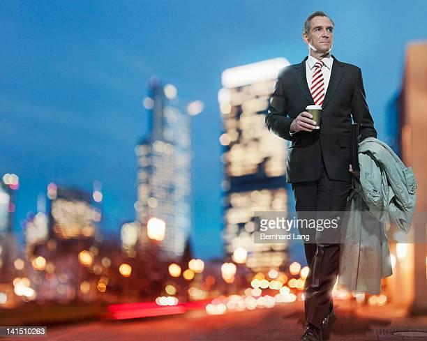 Businessman walking down urban street