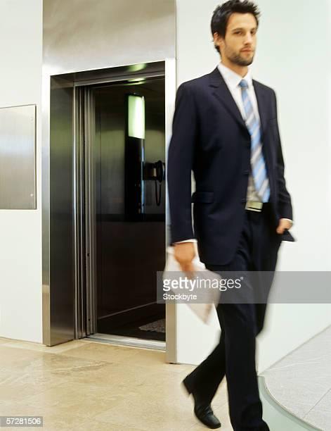 Businessman walking holding a newspaper