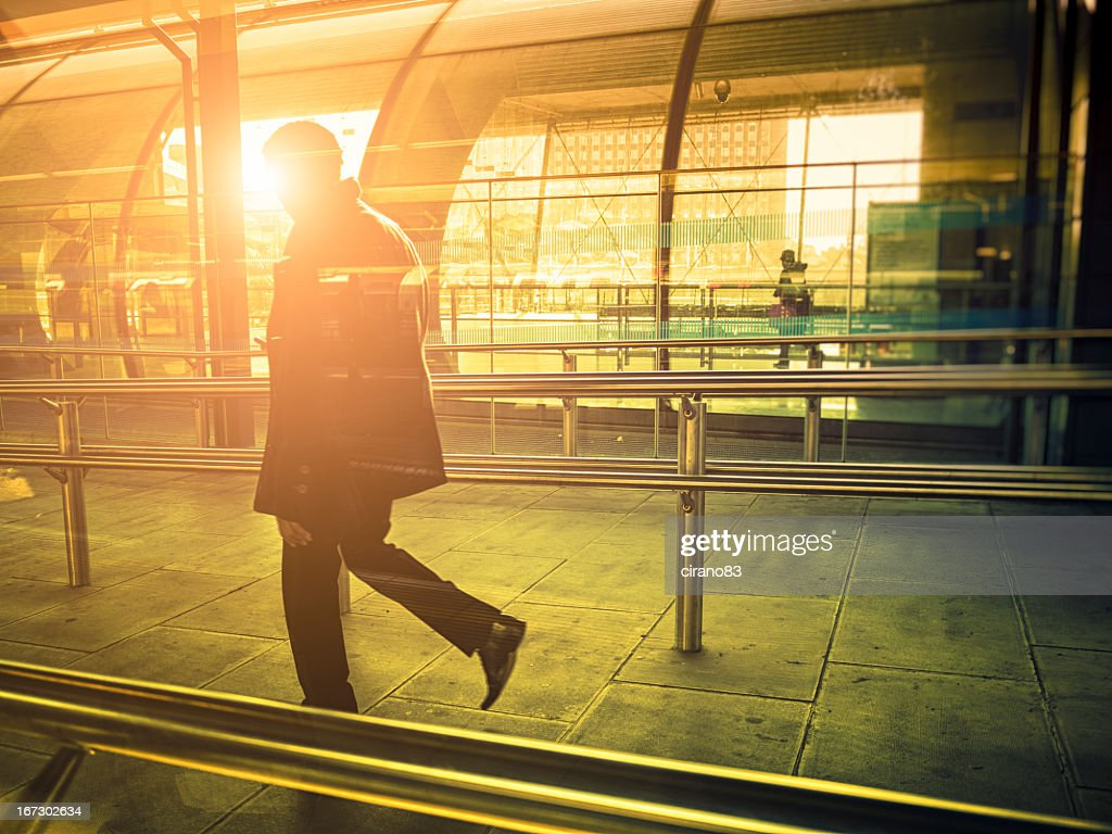 Businessman walking in a contemporary station against sunlight, London