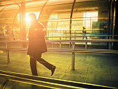 Businessman walking in a contemporary station against sunlight, London.