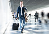 Businessman talking on phone and rushing in airport, blurred background