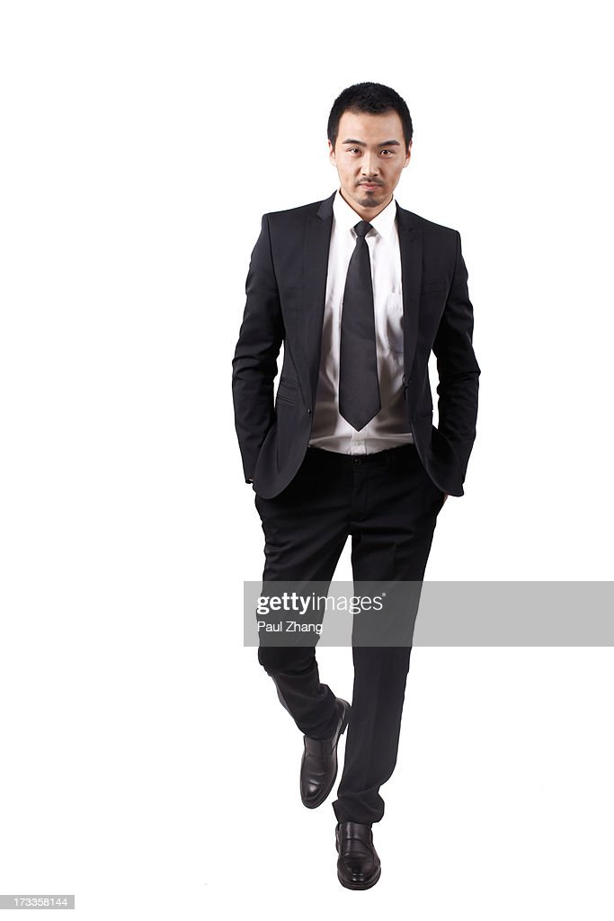 Businessman walking in black suit : Stock Photo