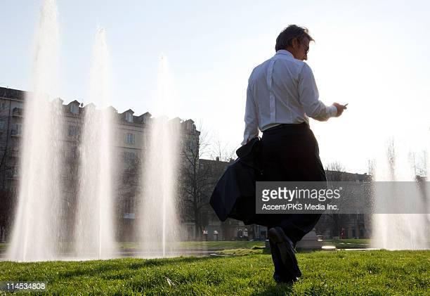 Businessman walking in city park, sending text