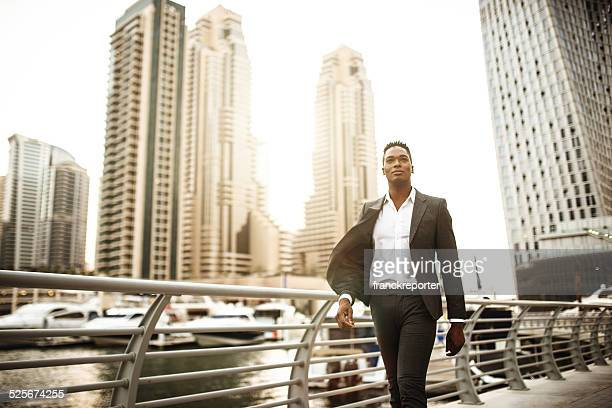 Homme d'affaires marchant dans le port de plaisance de Dubaï