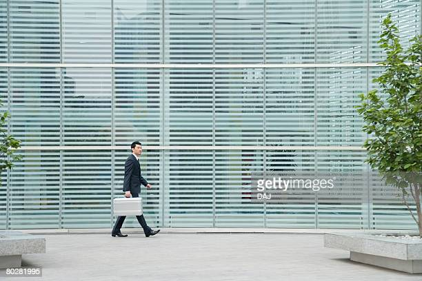 Businessman Walking in front of Building, China, Beijing