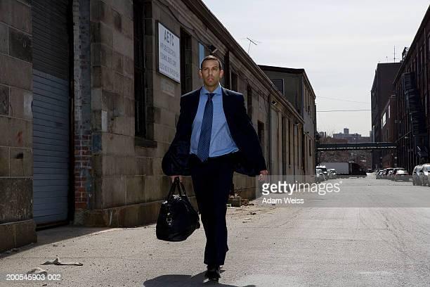 Businessman walking in industrial area