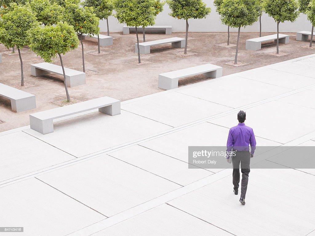 Businessman walking in modern courtyard : Stock Photo