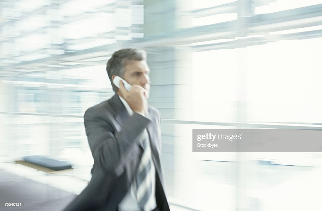 Businessman walking in office corridor,talking on mobile phone,blurred motion : Stock Photo