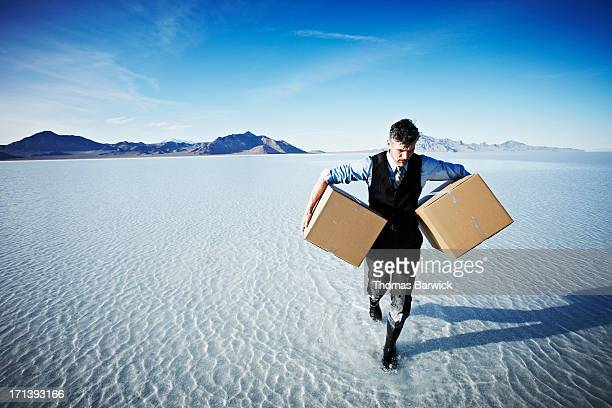 Businessman walking in shallow water with boxes