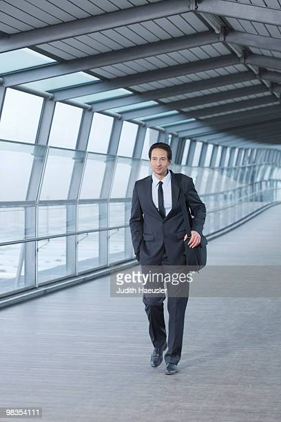 businessman walking in skywalk