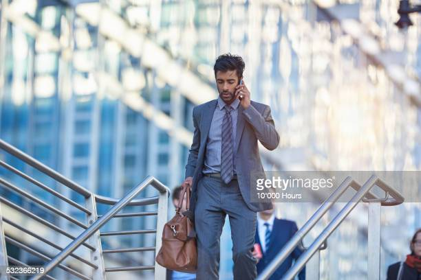 Businessman walking in the city, talking on phone