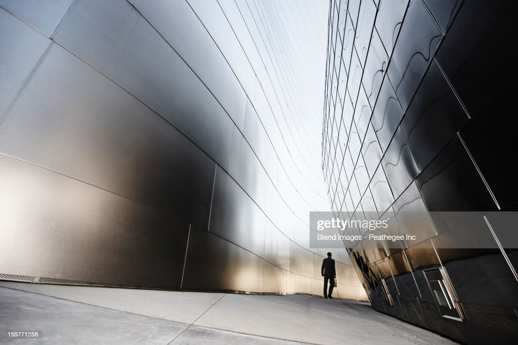 Businessman walking in urban alley : Stock Photo