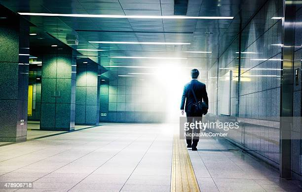 Businessman walking into the light end of tunnel