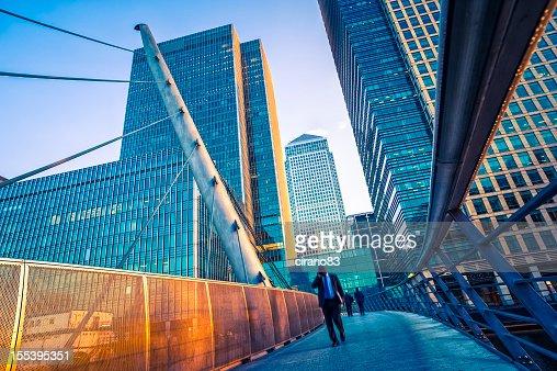 Geschäftsmann zu Fuß auf eine moderne Brücke in Canary Wharf, London