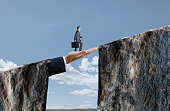 A businessman holds his briefcase as he walks across a large hand that bridges the gap between two cliffs.