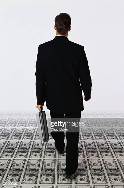 Businessman Walking on Hundred Dollar Bills