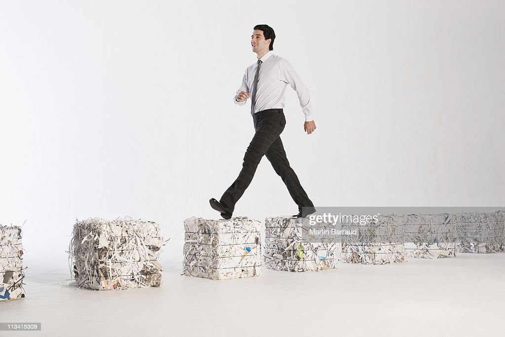 Businessman walking on paper bales : Stock Photo