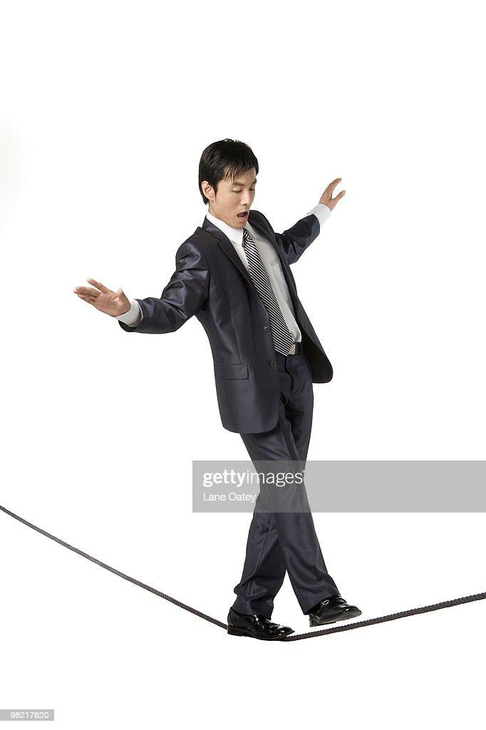 Businessman walking on rope in mid-air