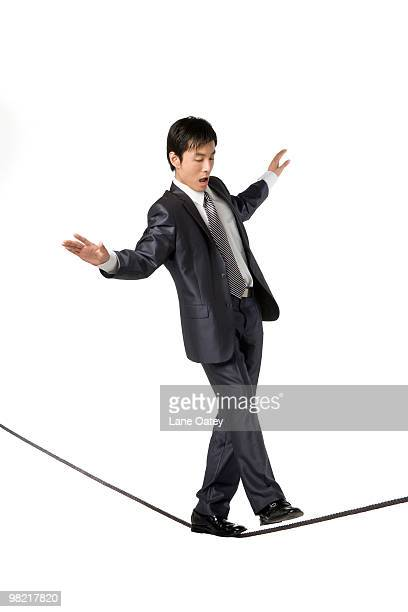 Businessman walking on rope in mid-air
