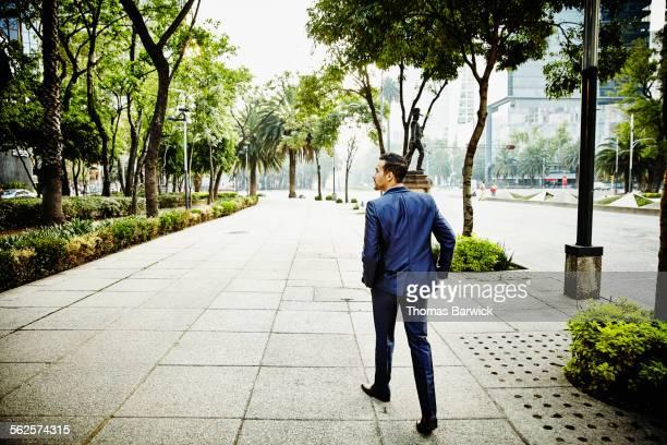 Businessman walking on sidewalk of city street