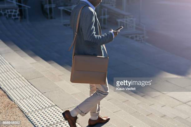 Businessman walking on staircase with bags