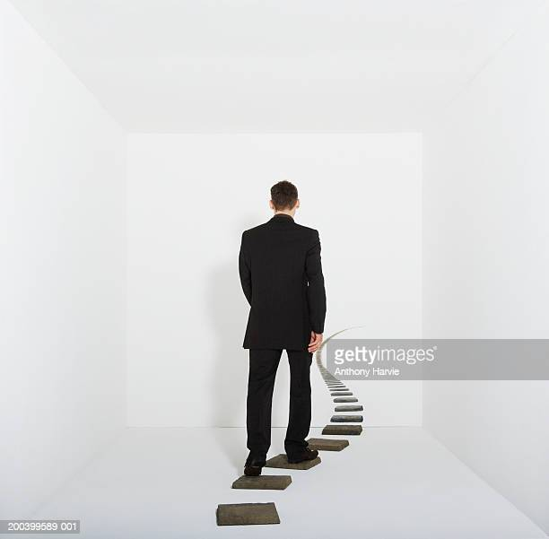 Businessman walking on stepping stones in white room, rear view