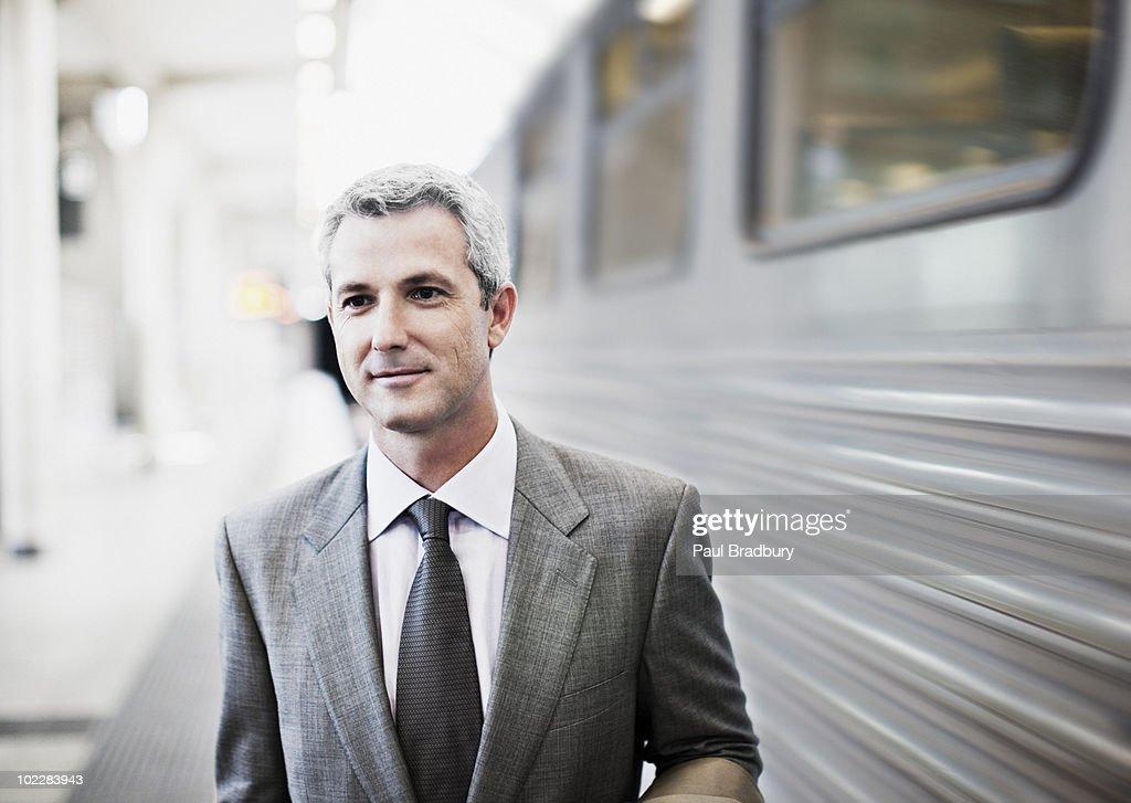 Businessman walking on train platform : Stock Photo