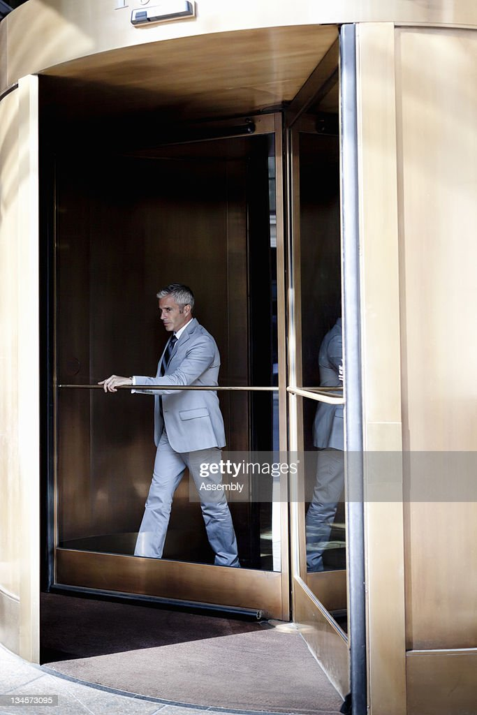 Businessman walking out of a revolving door. : Stock Photo