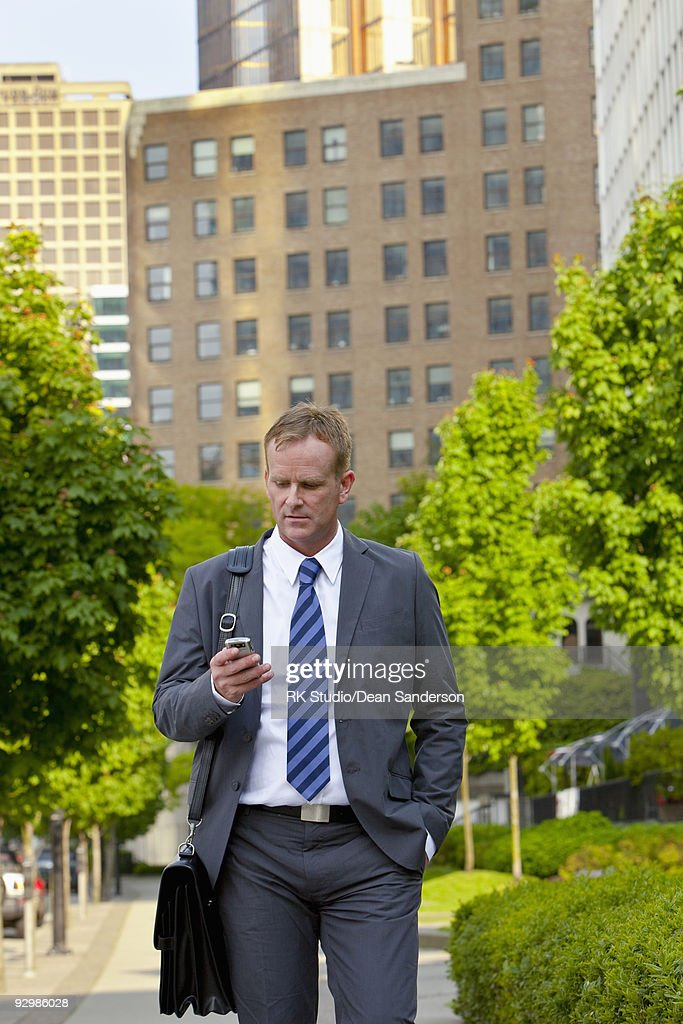 Businessman walking outdoors looking at phone. : Stock Photo