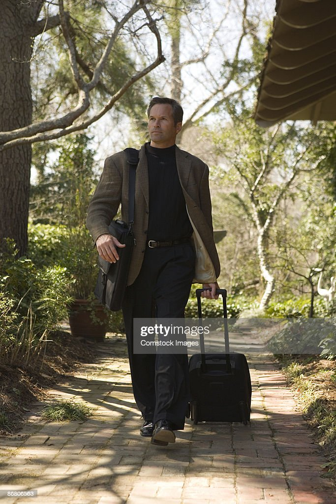 Businessman walking outdoors with luggage : Stock Photo
