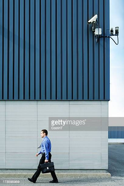 Businessman walking outside in front of security camera