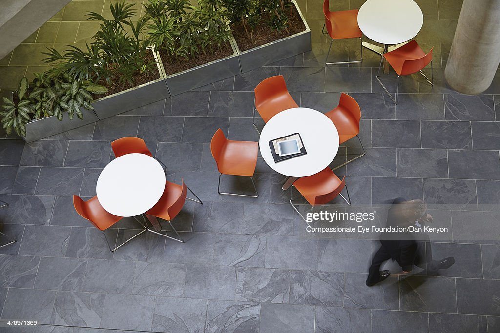 Businessman walking passed tables, blurred motion : Stock Photo