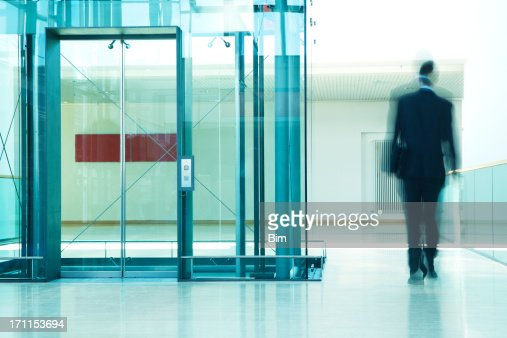 Businessman Walking Past Elevator in Modern Office Building, Motion Blur