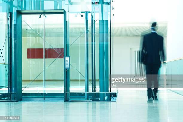 ビジネスマンの入ったエレベーターの近代的なオフィスビル、モーションブラー