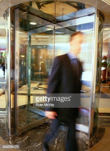 Businessman Walking Through a Revolving Door