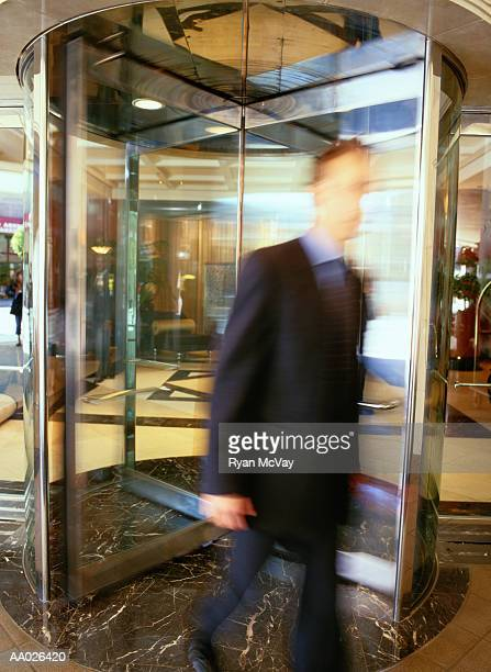 Businessman Walking Through a Revolving Door