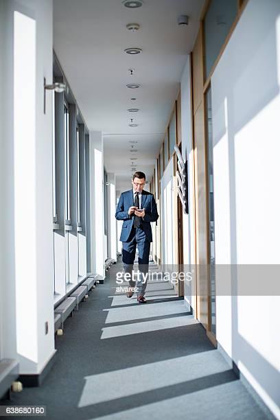 Businessman walking through corridor using mobile phone