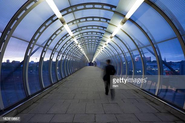 Geschäftsmann zu Fuß durch gläserne Fußgängerbrücke in der Dämmerung