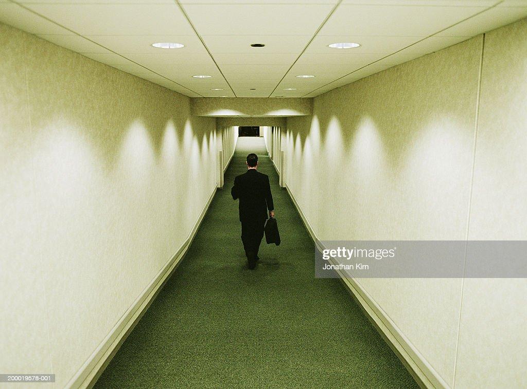 Businessman walking through tunnel, rear view : Stock Photo