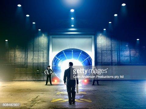 Businessman walking to tunnel in hangar