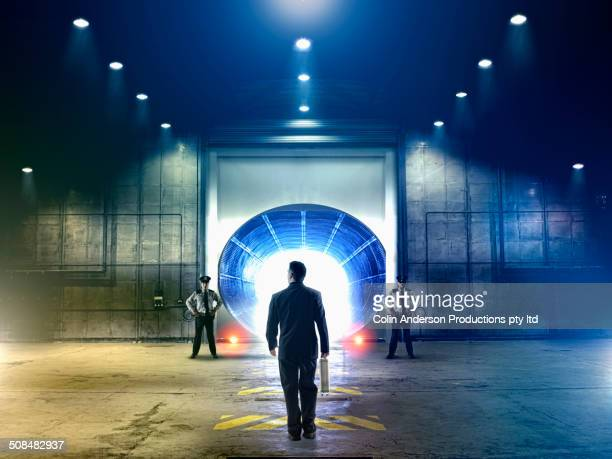Businessman walking to tunnel in hangar