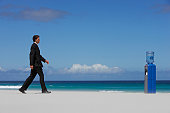 Businessman Walking Towards a Water Cooler on a Beach