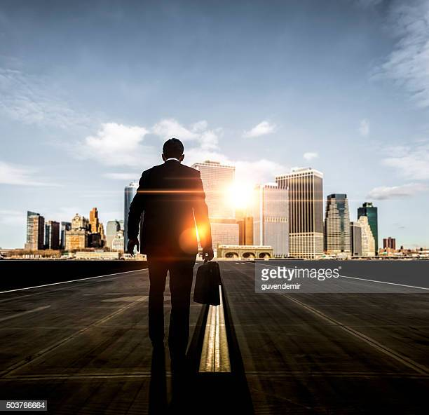 Businessman walking towards futuristic city